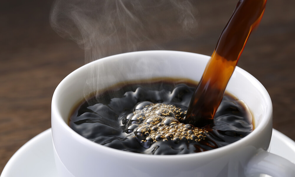 steaming hot coffee being poured into a white coffee cup