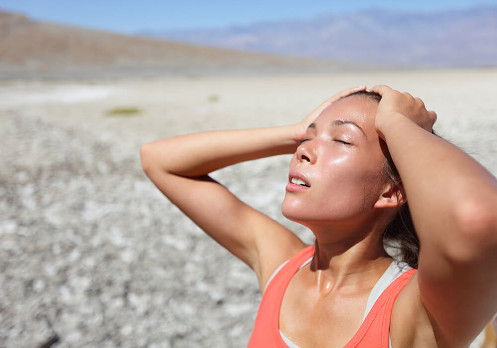 asian woman hot, sweaty, and dehydrated in desert