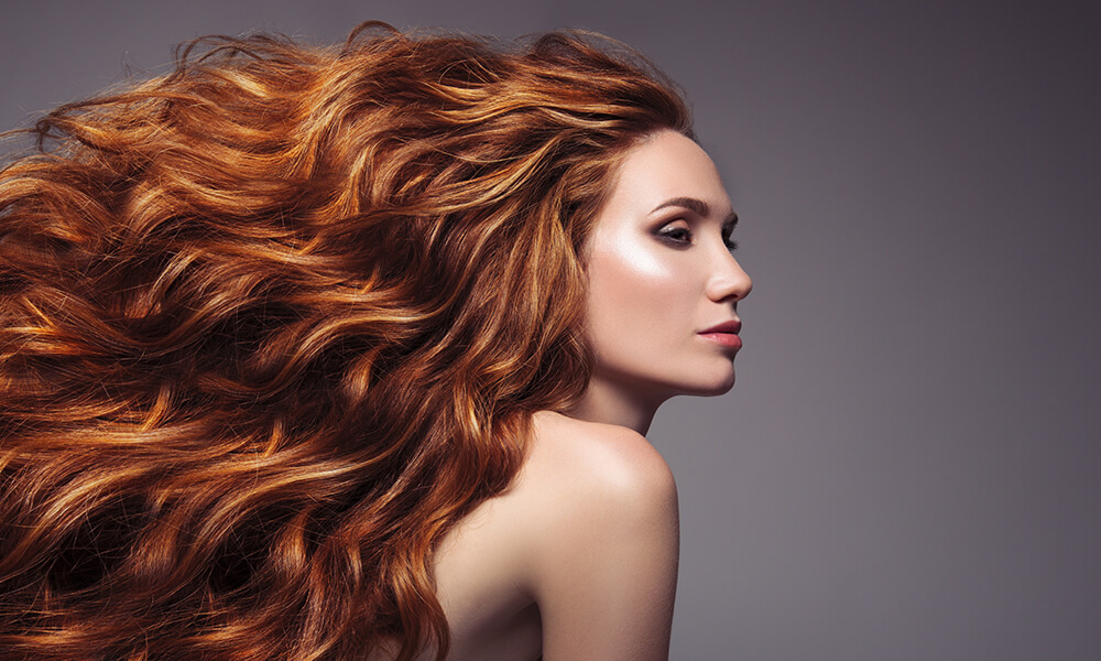 profile portrait of woman with voluminous silky red hair
