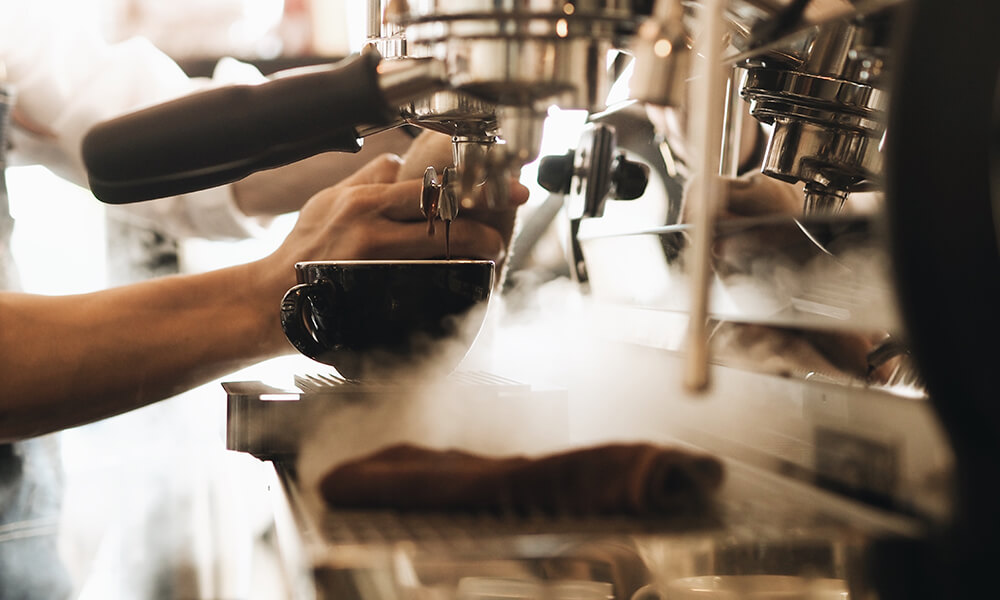 a barista making espresso, which tastes better with water filtration