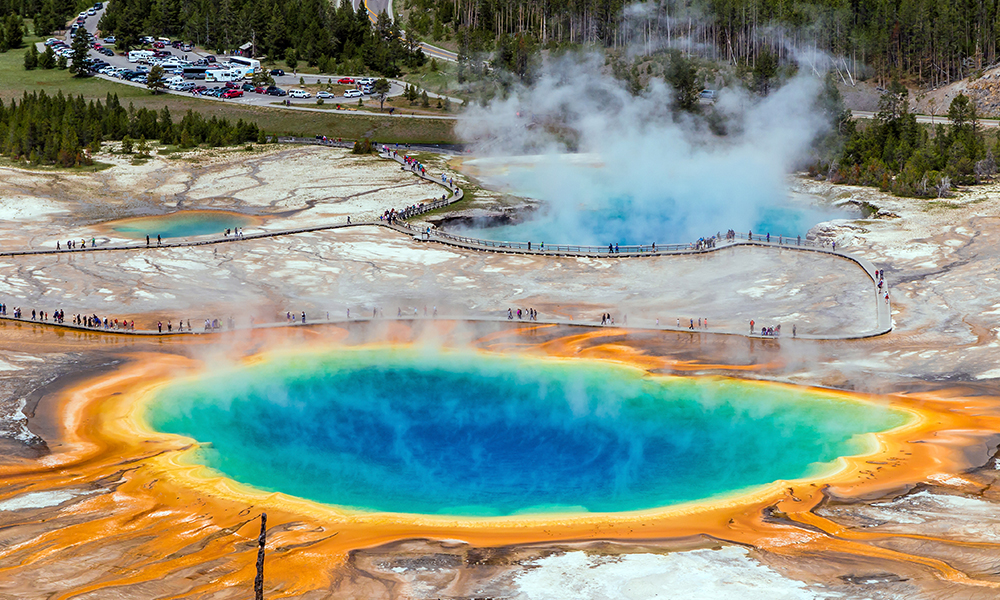 an aerial shot of the Grand Prismatic Spring, one of many beautiful bodies of water in the world