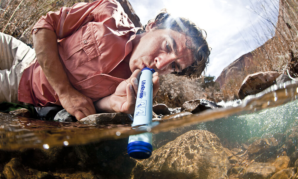 man drinking water from a lifestraw