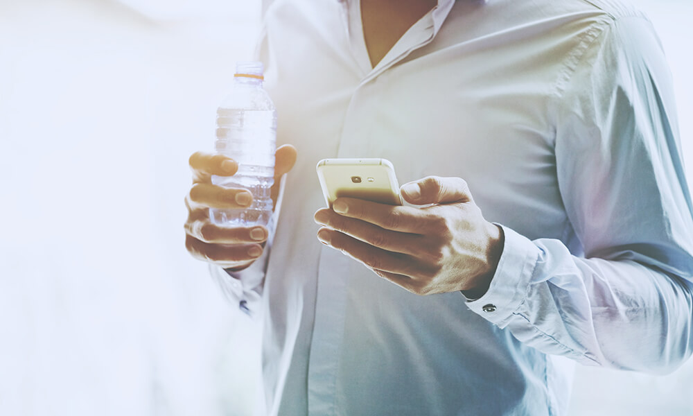 man wearing button up shirt holding phone and drinking a bottle of water to stay hydrated