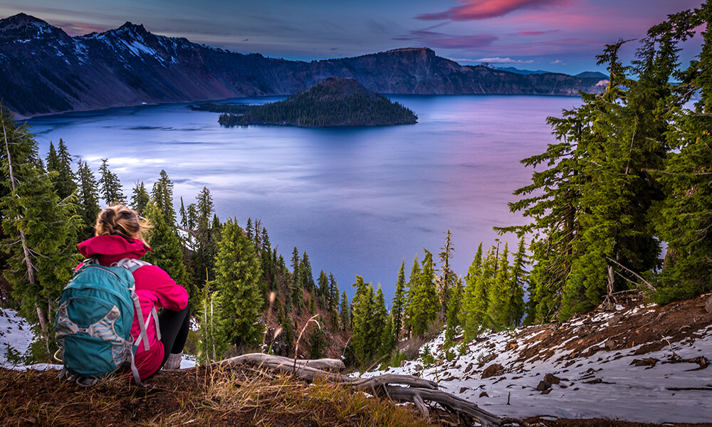 a hiker overlooking crater lake in the united states of america