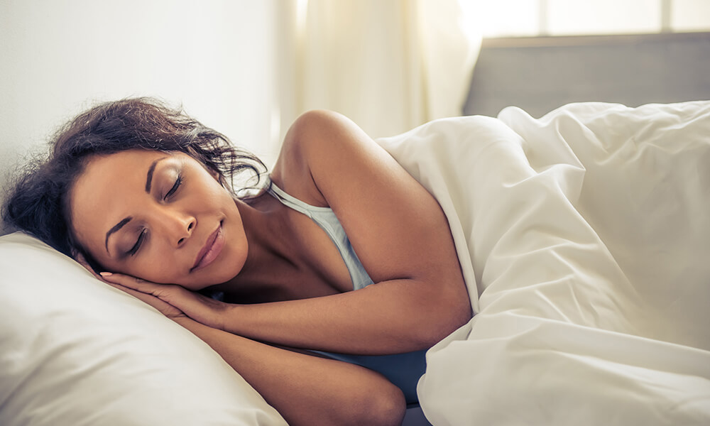 a woman laying on her side, sleeping in bed. A cause of dehydration