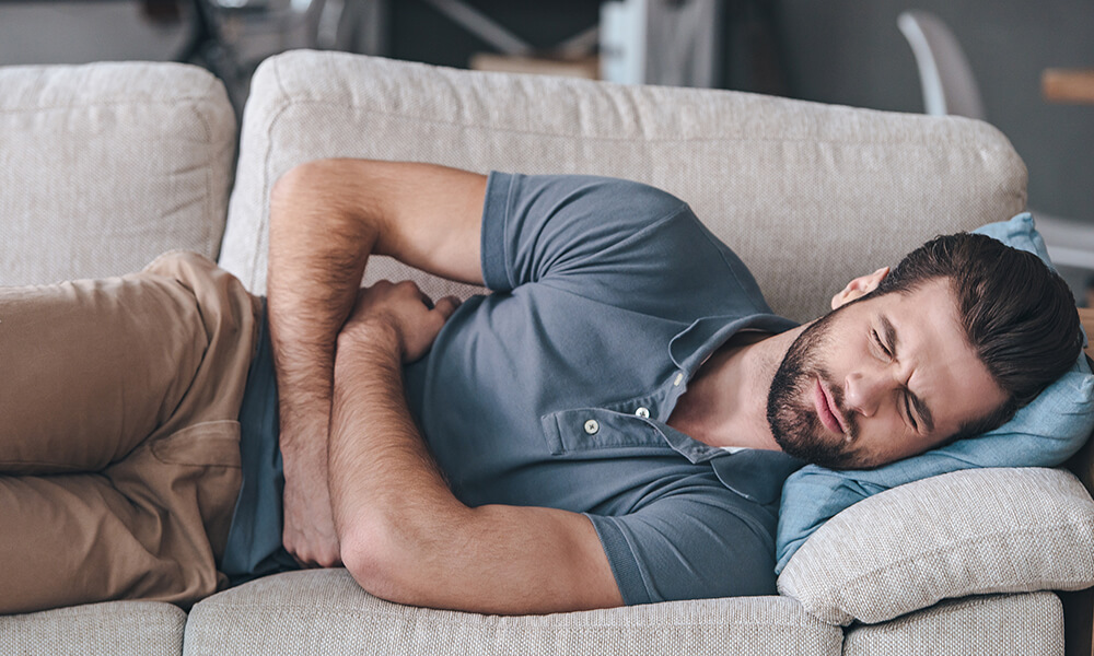 a man curled up on his couch clutching his upset stomach