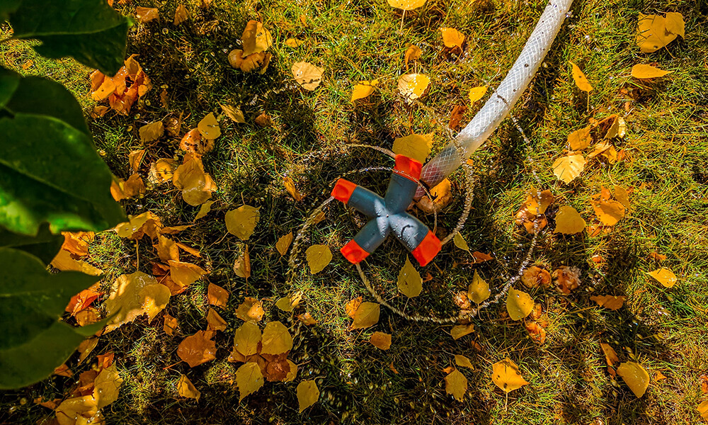 a small spinning water sprinkler watering an autumn lawn sprinkled with leaves