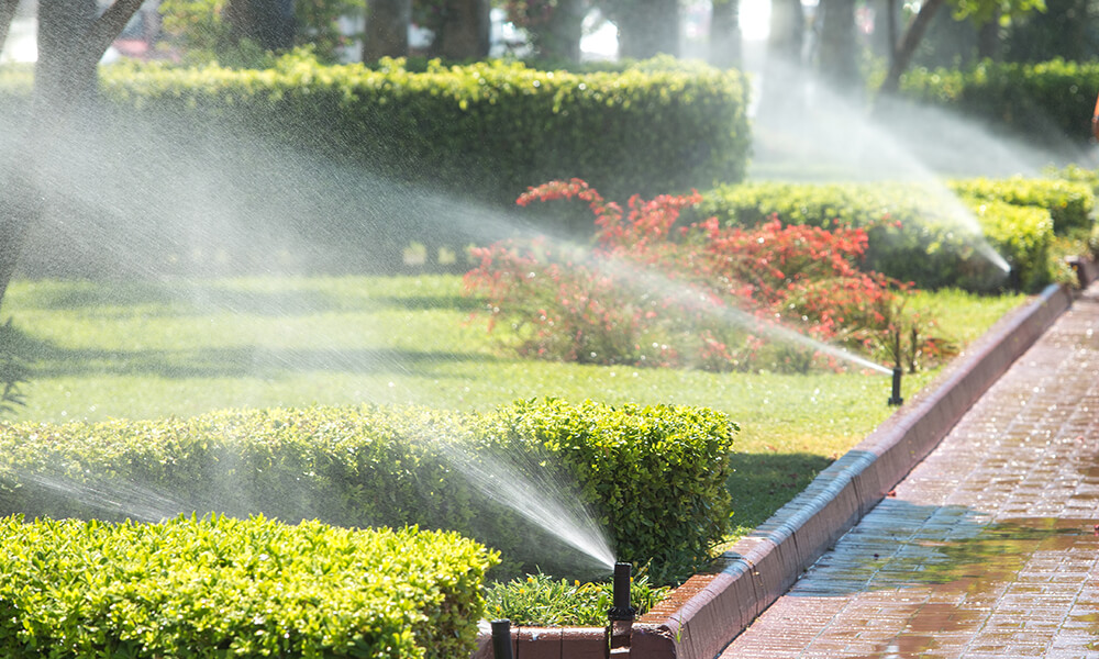 in-ground sprinklers spraying water over a well manicured lawn